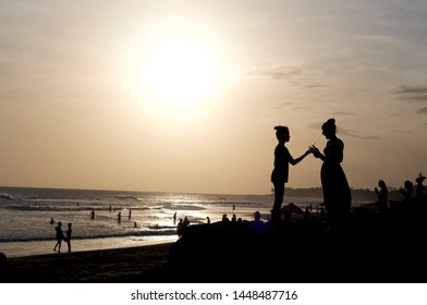 Canggu, Bali, Indonesia - 31st May 2019 : Silhouette picture of two women handling with a smart phone during sunset at the famous Echo Beach in Canggu, Bali - Indonesia