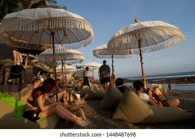 Canggu, Bali, Indonesia - 6th June 2019 : Tourists enjoy themselves on the beach bean bag at the famous Echo Beach during sunset in Canggu, Bali - Indonesia