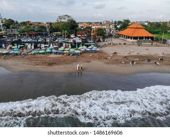 Canggu, Bali, Indonesia - Feb 15 2019: Aerial view of Canggu beach with surfers and umbrellas located in the west of Bali