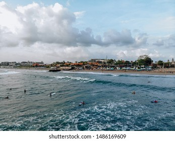 Canggu, Bali, Indonesia - Feb 15 2019: Aerial view of man on surfboard catching wave on Canggu beach located in the west of Bali on sunset with beautiful sky