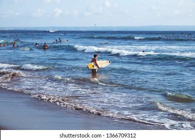 Canggu, Bali, Indonesia - January 11, 2019: People surfing in the ocean