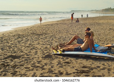 CANGGU, BALI ISLAND, INDONESIA - JAN 19, 2017: Surfers relaxing with surfboard on the beach. Bali island is one of the worlds best surfing destinations