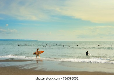 CANGGU, BALI ISLAND, INDONESIA - JAN 19, 2017: Surfers going to surf in the ocean. Bali island is one of the worlds best surfing destinations