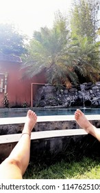 Canggu, Indonesia - 07 18 2018: Woman and man relaxing at the hotel pool in Canggu