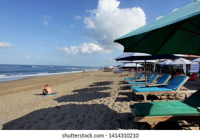 Canggu, Indonesia - May 27, 2019: Canggu Surf beach during the day with a tourist sitting enjoy the solitude of sunbathing looking at the sea view at Canggu Beach in Bali, Indonesia