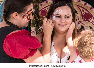 Cangy, Oregon - June 9, 2019: Woman holding a small child while having her face painted at a Renaissance Fair.
