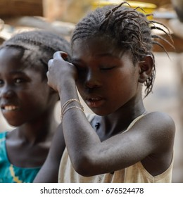 CANHABAQUE, GUINEA BISSAU - MAY 4, 2017: Unidentified local girls stand in a village of the Canhabaque island. People in G.-Bissau still suffer of poverty