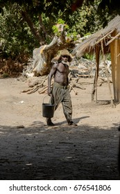 CANHABAQUE, GUINEA BISSAU - MAY 4, 2017: Unidentified local man with beard in a hat walks with a bucket in a village of the Canhabaque island. People in G.-Bissau still suffer of poverty