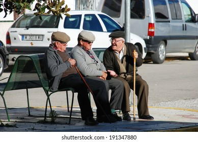 Canillas de Aceituno, Spain - February 13, 2009 - Three elderly Spanish men sitting on a bench chatting, Canillas de Aceituno, Malaga Province, Andalusia, Spain, Western Europe, February 13, 2009.