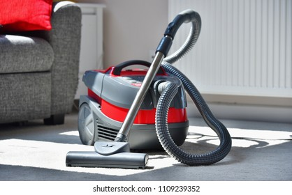 Canister vacuum cleaner for home use on the floor in the apartment.