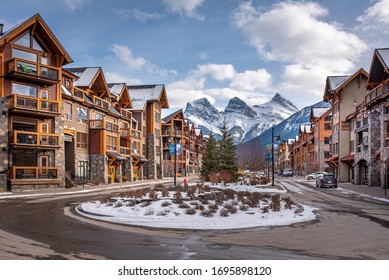 Canmore, Alberta - April 4, 2020:  Luxury condominiums in the town of Canmore Alberta during the winter. Three Sisters mountain is visible in the distance.