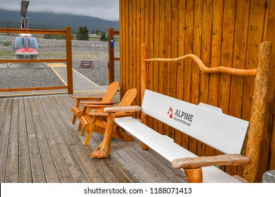 CANMORE, ALBERTA, CANADA - JUNE 2018: Wooden seating outside the terminal building of Alpine Helicopters base in Canmore. A Bell 206 Longranger helicopter is in the background.