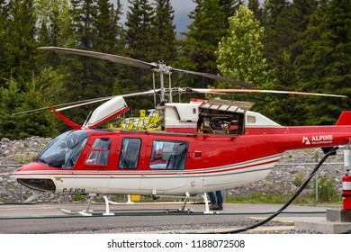 CANMORE, ALBERTA, CANADA - JUNE 2018: Bell 407 helicopter operated by Alpine Helicopters from its base in Canmore. Its engine cover is open for maintenance.