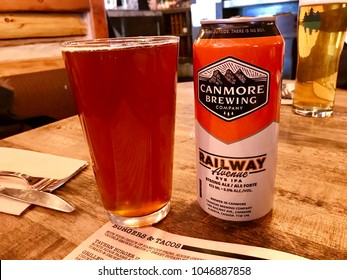 Canmore, Alberta - March 12 2018: A can of Canmore Brewing Company beer beside a full pint glass on a wooden restaurant table with a place setting and menu