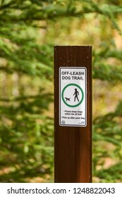 CANMORE, CANADA - MAY 2018: Sign on a  footpath through a wooded area in Canmore informing dog owners they can take their dog off its leash.