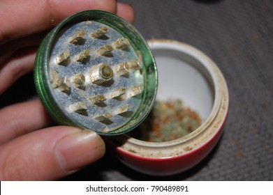 Cannabis being mixed with tobacco, from grinder into a small cointainer