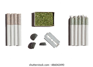 Cannabis in box.Four rolled cigarettes with tobacco, five with hemp, box with cannabis , blade and stones lay on the white table.