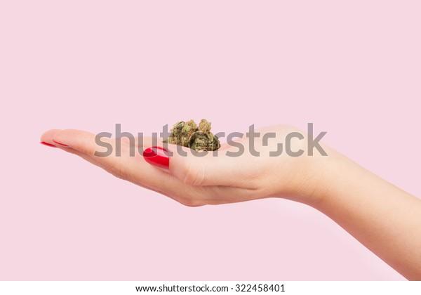 Boue de cannabis à la main de la femme avec des ongles rouges isolée sur fond rose. Toxicomanie chez les adolescents.