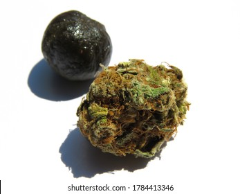 Cannabis bud with hashish ball in the background.