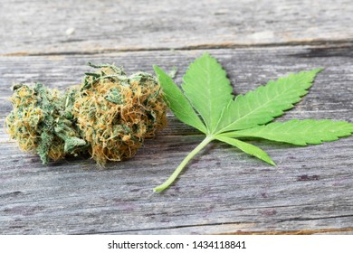 Cannabis bud and cannabis leaf on wooden surface.