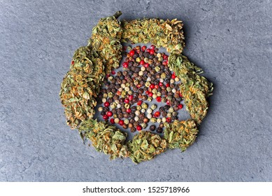 Cannabis buds circle with four color pepper. Caryophyllene terpene concept on grey background.