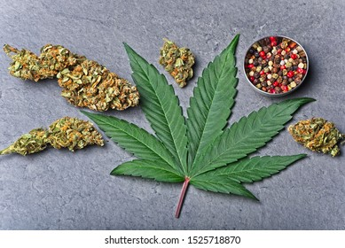 Cannabis buds and leaf with red color pepper in small bowl. Caryophyllene terpene concept on grey background.