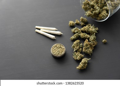 Cannabis buds on black table, grinder with fresh marijuana, close up, joint with weed,