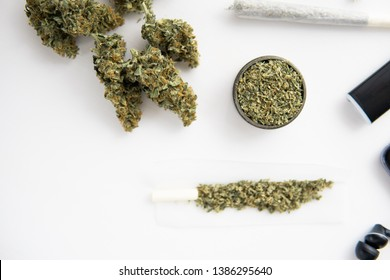 Cannabis buds on black table, close up, joint with marijuana, grinder with fresh weed,