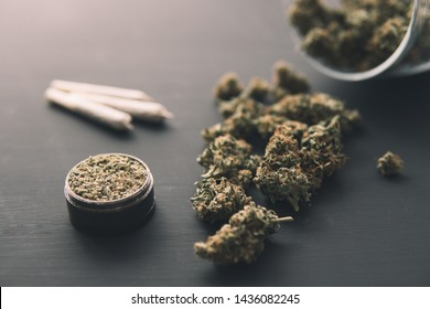 Cannabis buds on black table, grinder with fresh marijuana, joint with weed, top view close up,