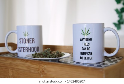 Cannabis buds on a plate next to two 420 friendly mugs on a breakfast tray. The wake and bake mugs say 'stoner sisterhood' and 'anything trees can do hemp can do better.'
