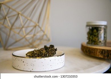 Cannabis Buds on Tray with Marijuana Shake in Glass Jar in Background - Cannabis Dispensary Products