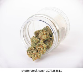 Cannabis buds (sour tangie strain) isolated on white inside a glass jar - Medical marijuana background