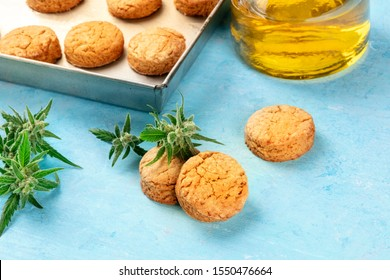Cannabis butter cookies with marijuana buds and cannaoil, homemade healthy biscuits, close-up shot on a blue background