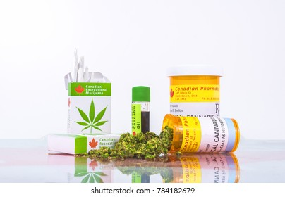 Cannabis in Canada. Marijuana cigarettes, cannabis oil, and prescription bottles for cannabis on a glass table. Buds spill from one of the bottles. Red maple leaf under the glass.