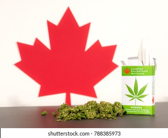 Cannabis in Canada. A package of cannabis cigarettes on a table, with a Canadian maple leaf behind. Marijuana buds on the table.