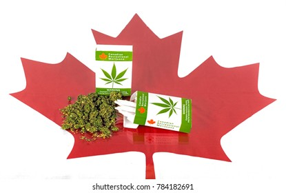 Cannabis in Canada. Two packages of marijuana cigarettes with buds lying on a glass table. A maple leaf is under the glass. Joints stick up from one package.