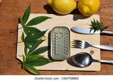 Cannabis with canned food on wooden table.