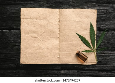 Cannabis cbd oil recipe blank book with a copy space, cbd oil in a bottle and green leaves on a black wooden table background.