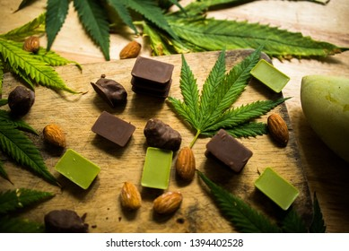 cannabis chocolate on wooden background and marijuana leaf