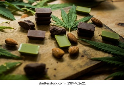 cannabis chocolate on wooden background and marijuana leaf