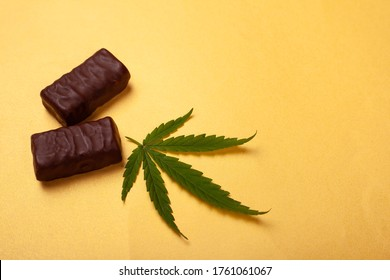 cannabis chocolates on yellow background, green leaf and candy.