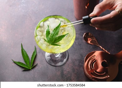 Cannabis cocktail margarita infused with CBD with marijuana leaf on dark background