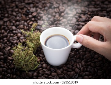 Cannabis coffee. Hand grabbing an ear cup of hot espresso as beside cannabis buds lay on many roasted coffee beans.
