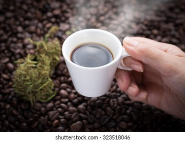 Cannabis coffee. Hand grabbing an ear cup of hot espresso as beside cannabis buds also see many roasted coffee beans on a floor.