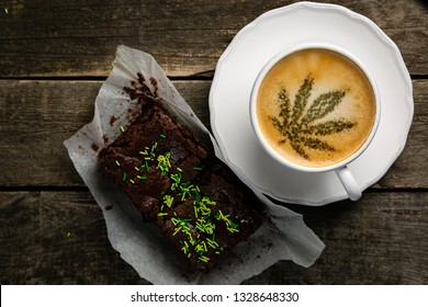 Cannabis coffee - marijuana leaf on coffee foam, rustic wood background