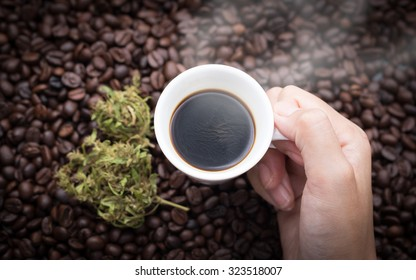 Cannabis coffee. Top view of hand grabbing an ear cup of hot espresso as beside cannabis buds also see many roasted coffee beans on a floor.