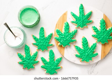 Cannabis cookies overhead on white marble. THC or CBD baking weed cookies flat lay. Cannabis edibles for medical or recreational consumption. Made with cannabis infused oil and royal icing.