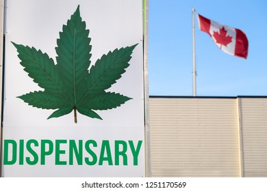 A cannabis dispensary sign with a large marijuana leaf on it and a Canadian flag in the background.