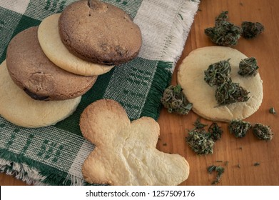 Cannabis edible: Cookies made with marijuana. Cookies with THC. Homemade cookies on a cloth napkin and a pile of marijuana buds on wooden table.