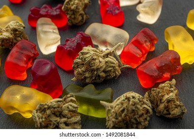 Cannabis edibles, medical marijuana, CBD infused gummies and edible pot concept theme with close up on colorful gummy bears and weed buds on dark background